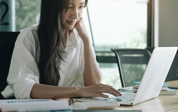Bliska biznes kobieta lub księgowy ręka trzyma ołówek pracujący na kalkulatorze do obliczenia raportu danych finansowych, dokumentu księgowego i laptopa w biurze, koncepcja biznesowa