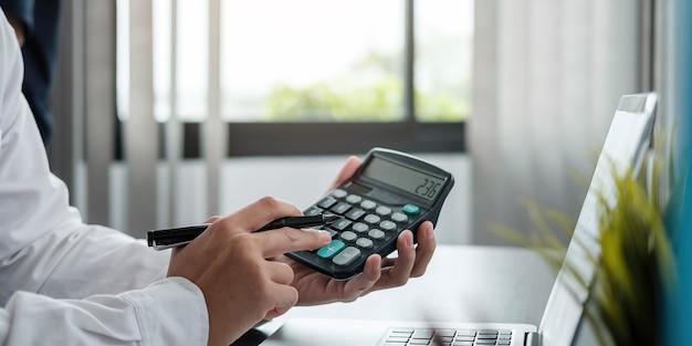 Bliska biznes kobieta za pomocą kalkulatora i laptopa do matematyki finansów na drewnianym biurku w pracy biurowej i biznesowej, podatkowej, księgowej, statystycznej i analitycznej koncepcji badawczej