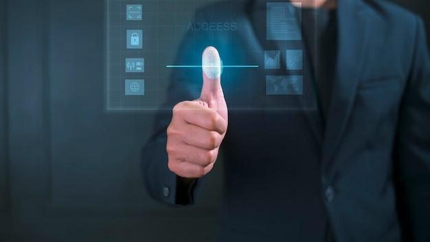 Bliska biznesmen dotyka interfejsu monitora komputera, tożsamości biometrycznej odcisków palców i zatwierdzenia. przyszłe bezpieczeństwo i kontrola haseł za pomocą technologii odcisków palców i cybernetycznego biznesu