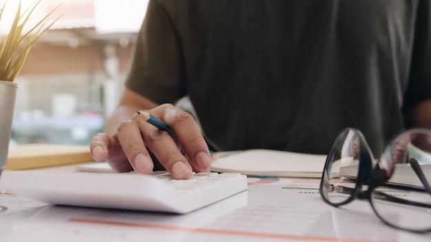 Bliska biznesmen lub księgowy ręka trzyma pióro pracujące na kalkulatorze do obliczania danych biznesowych, dokumentu księgowego i laptopa w biurze, koncepcja biznesowa