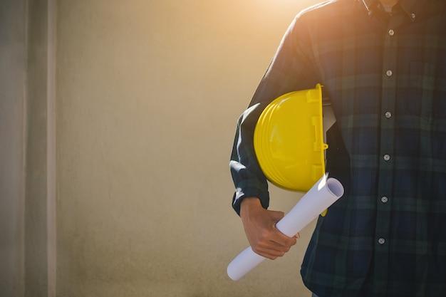 Bliska biznesmen posiadający żółty twardy kapelusz budowniczy osiedla budowlanego