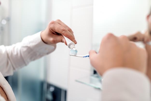 Bliska biznesmen wprowadzenie pasty do zębów na szczoteczce, stojąc w łazience.