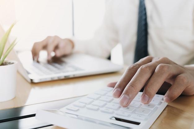Bliska biznesmen za pomocą kalkulatora i laptopa do finansów matematycznych na drewnianym biurku w biurze