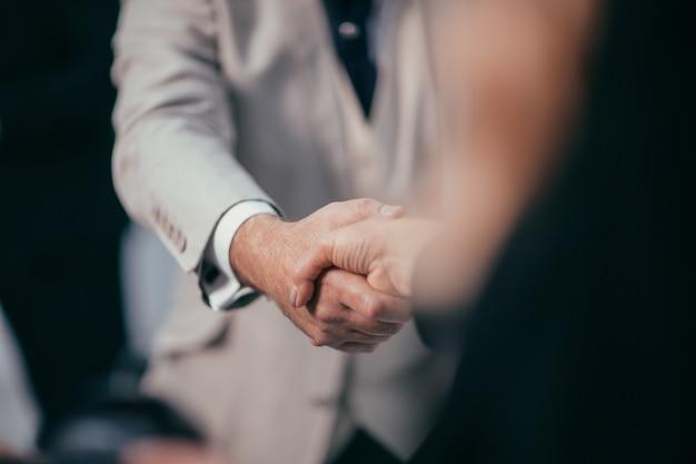 Bliska biznesowy uścisk dłoni na tle biurowym
