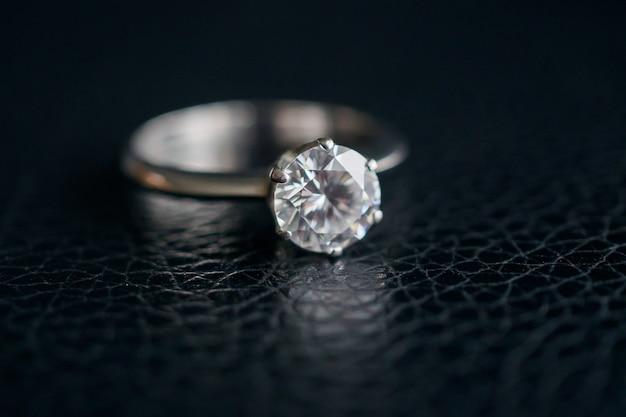 Bliska biżuteria pierścionek z brylantem na czarnej skórze