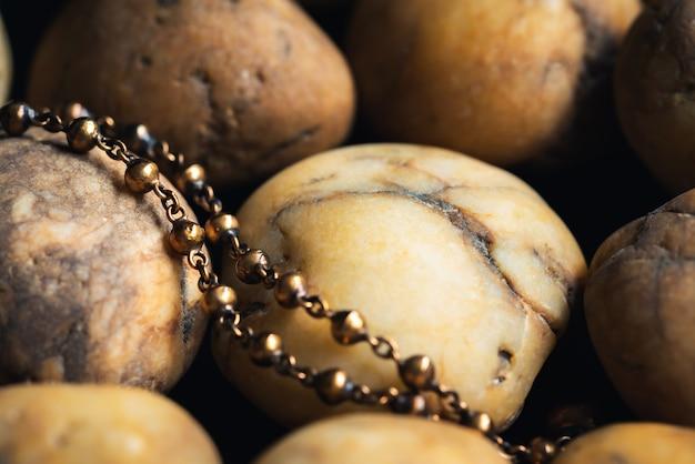 Bliska biżuteria z mosiądzu na tle żwiru rzecznego. vintage naszyjnik, starożytna biżuteria, używana do tła vintage