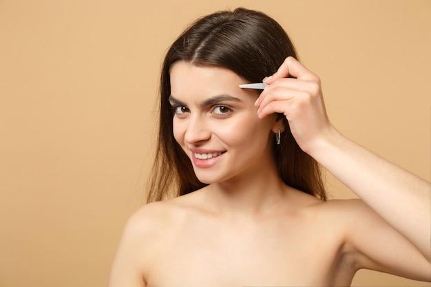 Bliska brunetka pół naga kobieta 20s z idealną skórą, nago makijaż na białym tle na beżowej pastelowej ścianie, portret. koncepcja zabiegów kosmetycznych opieki zdrowotnej opieki zdrowotnej.