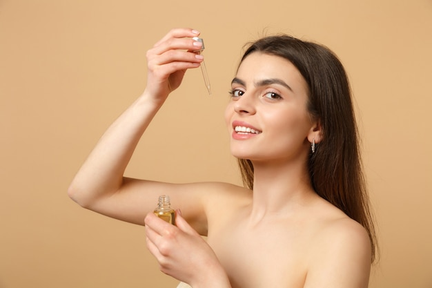 Bliska brunetka półnaga kobieta o idealnej skórze, nagi makijaż nakłada olej z butelki na twarz odizolowaną na beżowej pastelowej ścianie