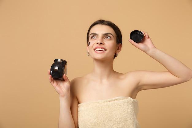 Bliska brunetka półnaga kobieta z idealną skórą, naga makijaż czarna maska odizolowana na beżowej pastelowej ścianie