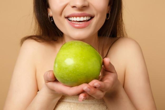 Bliska brunetka półnaga kobieta z idealną skórą, nagi makijaż trzyma jabłko na białym tle na beżowej pastelowej ścianie