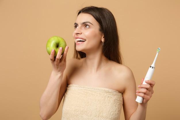 Bliska brunetka półnaga kobieta z idealną skórą, nagi makijaż trzyma pędzel na beżowej pastelowej ścianie