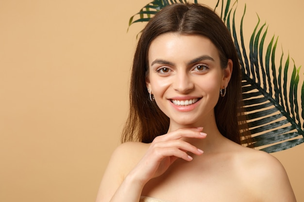 Bliska brunetka półnaga kobieta z idealną skórą, nagim makijażem i liściem palmowym na beżowej pastelowej ścianie