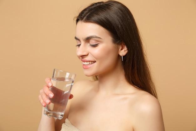 Bliska brunetka półnaga kobieta z idealną skórą nago tworzy szklaną wodę odizolowaną na beżowej pastelowej ścianie