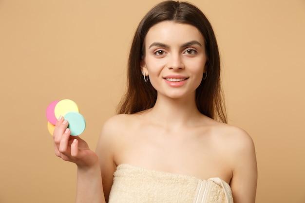 Bliska brunetka półnaga kobieta z idealną skórą, usuwająca nagi makijaż odizolowany na beżowej pastelowej ścianie