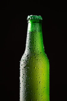 Bliska butelka zimnego piwa z kropli wody na białym tle na czarnym tle. format pionowy.