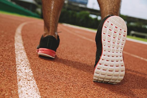 Bliska butów fitness ludzie biegacz sportowiec działa na drodze na wschód słońca w publicznym parku. koncepcja odnowy biologicznej treningu fitness i ćwiczeń. nieostrość.