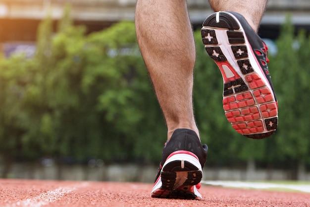 Bliska buty fitness ludzie biegacz sportowiec działa na drodze w publicznym parku. koncepcja odnowy biologicznej treningu fitness i ćwiczeń.
