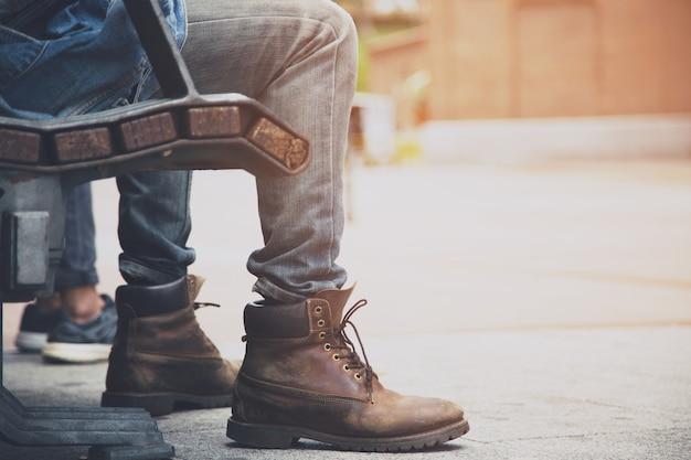 Bliska buty trampki niezidentyfikowani ludzie młody człowiek hipster siedzieć czekając na publicznym drewnianym krześle relaksując się w publicznym parku na świeżym powietrzu w centrum miasta.