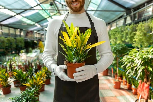 Bliska buźkę mężczyzny trzymającego roślinę