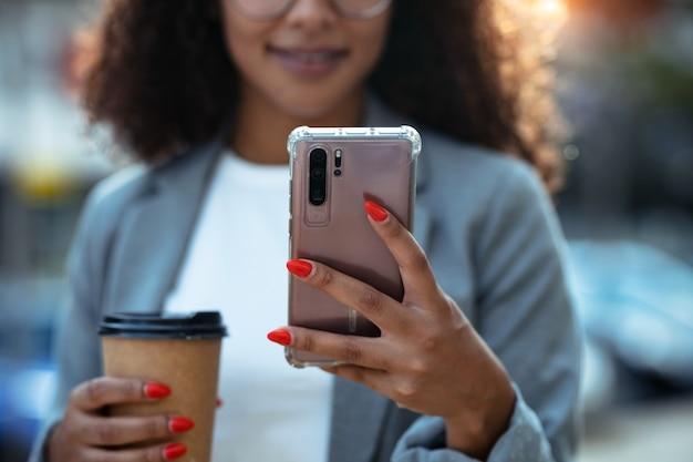 Bliska całkiem młoda kobieta biznesu za pomocą swojego inteligentnego telefonu podczas picia kawy idąc ulicą.