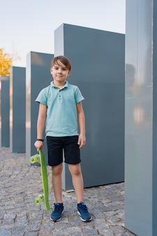 Bliska chłopiec na sobie niebieskie trampki ćwiczenia z zielonym deskorolka. aktywny miejski styl życia młodzieży, trening, hobby, aktywność. aktywny sport na świeżym powietrzu dla dzieci. dzieci na deskorolce.