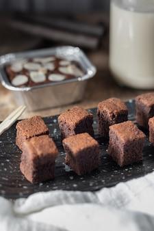 Bliska ciasto czekoladowe mini brownie, deser z mlekiem na ciemnym tle na drewnianym stole.