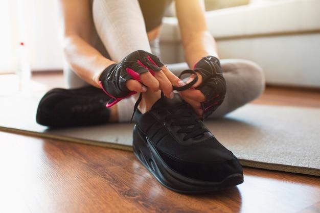 Bliska czarne stylowe trampki. kobieta wiązanie sznurówek i przygotowanie do treningu w domu.