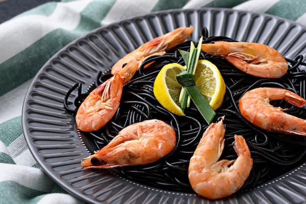 Bliska czarny makaron z tuszem mątwy z krewetkami królewskimi i klinami cytryny w szarym talerzu na ręcznik kuchenny, koncepcja kuchni śródziemnomorskiej
