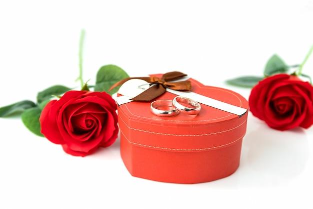 Bliska czerwona róża i pudełko w kształcie serca z obrączką na białym tle, koncepcja ślubu z różami i czerwonym pudełkiem w kształcie serca