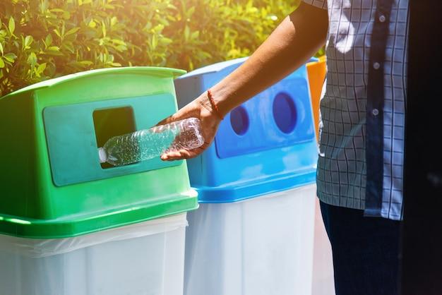 Bliska człowiek czarna ręka rzuca pustą plastikową butelkę wody w koszu recyklingu śmieci