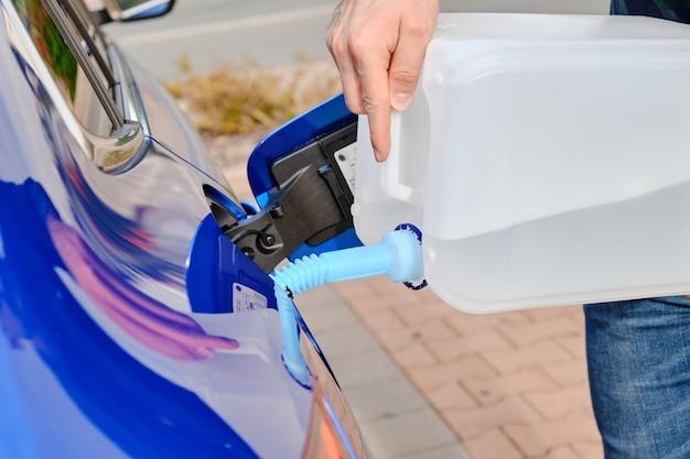 Bliska człowiek napełniający płyn silnika diesla z kanistra do zbiornika niebieskiego samochodu.