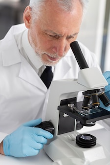 Bliska człowiek pracujący z mikroskopem