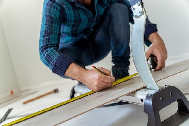 Bliska człowiek stolarz cięcia arkusza drewna, aby zainstalować drewnianą podłogę