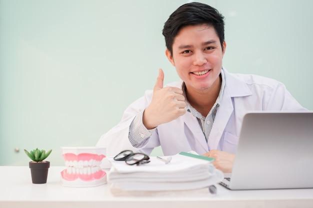 Bliska dentysta człowiek pokazać kciuk do góry na dobre zdrowie na biurku