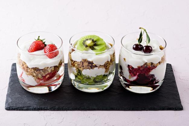 Bliska deser owocowo-jagodowy z bitym twarogiem, granolą, truskawkami, wiśniami i kiwi na czarnym kamieniu