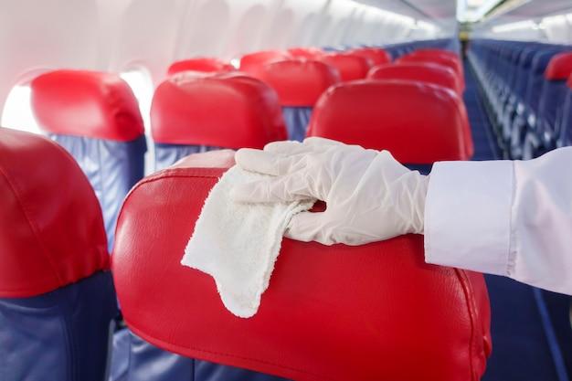 Bliska dłoń ma na sobie rękawiczki czyszczące fotele samolotu na wypadek pandemii zapobiegania covid-19
