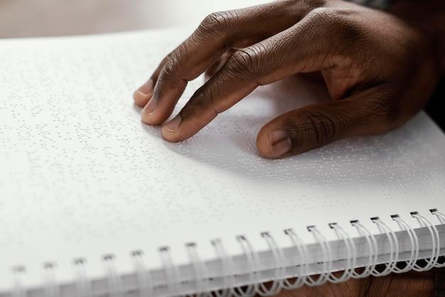 Bliska dłoń na notatniku braille'a