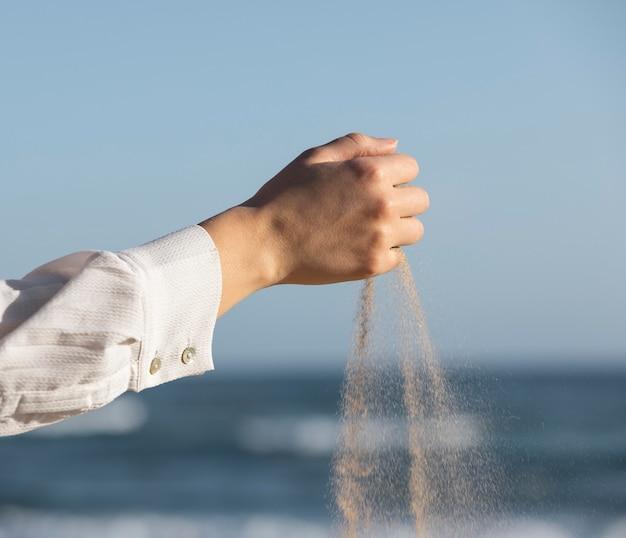 Bliska dłoń puszczająca piasek