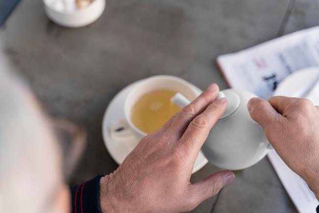 Bliska dłoń trzymająca czajniczek