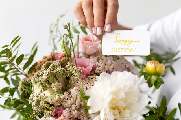 Bliska dłoń trzymająca kartkę z życzeniami urodzinowymi