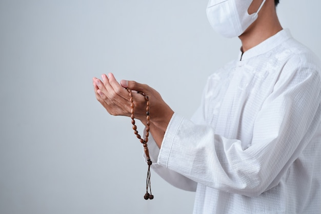 Bliska dłoń trzymająca koraliki lub tasbih z na szaro