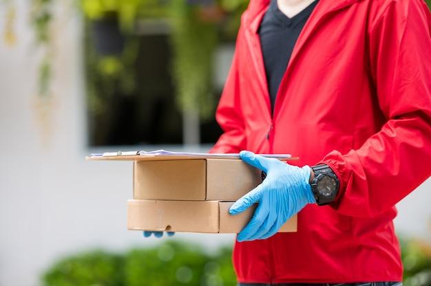 Bliska dostawa mężczyzna ma na sobie niebieskie rękawiczki w czerwonym szmatką, trzymając pudełko