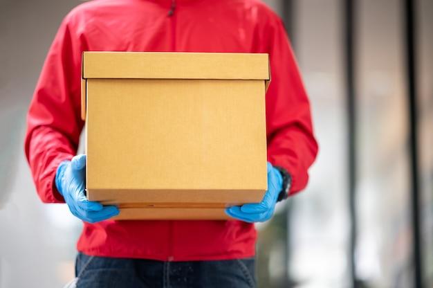 Bliska dostawy mężczyzna ma na sobie niebieskie rękawiczki i czerwoną kurtkę, trzymając karton
