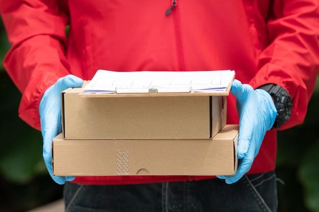 Bliska dostawy mężczyzna ma na sobie niebieskie rękawiczki i czerwoną kurtkę, trzymając kartony