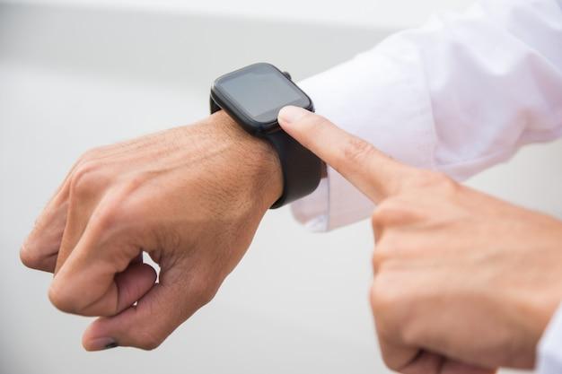 Bliska dotyk dłoni na technologii smartwatch