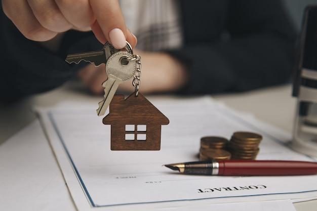 Bliska drewniany dom zabawki z kobietą podpisuje umowę zakupu lub kredyt hipoteczny na dom, pojęcie nieruchomości.