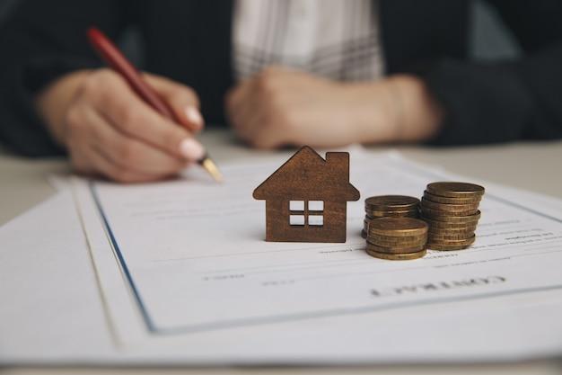 Bliska drewniany dom zabawki z kobietą podpisuje umowę zakupu lub kredyt hipoteczny na dom