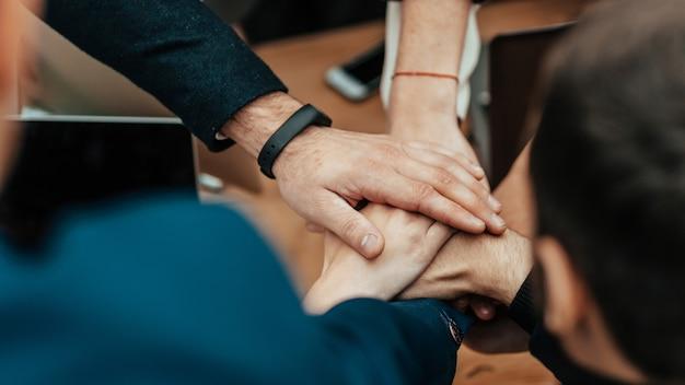 Bliska drużyna biznesowa składająca dłonie nad biurkiem