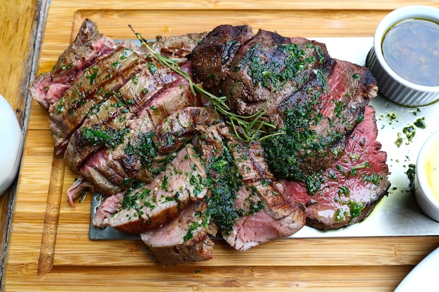 Bliska duża porcja pieczonej wołowiny chateaubriand z grilla z tymiankiem i ziołami podawana na drewnianej desce do krojenia, wysoki kąt widzenia