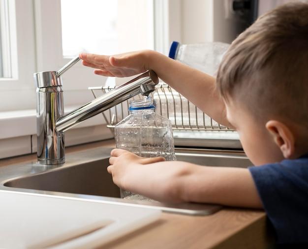 Bliska dziecko napełnianie butelką wodą